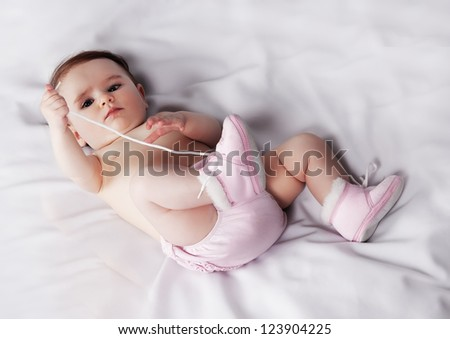 Portrait of a cute little girl playing with their feet - stock photo