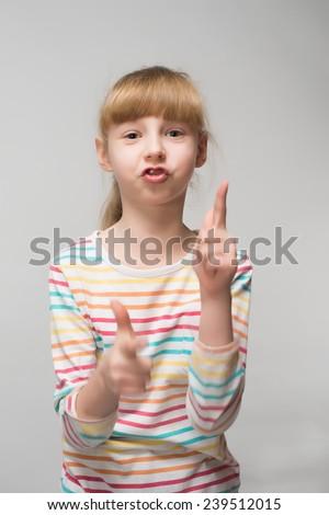 Portrait of a cute little girl's fingers gun - stock photo