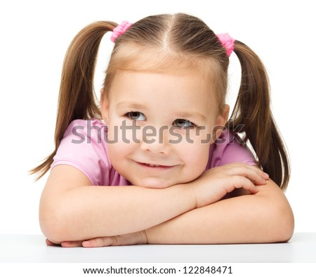 Portrait of a cute little girl sitting at table, isolated over white - stock photo