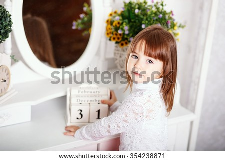 Portrait of a cute little girl sitting near a mirror with wooden calendar in the hands in the interior with Shabby chic decor  - stock photo