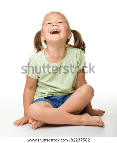 Portrait of a cute little girl sitting on floor, laughing, isolated over white - stock photo