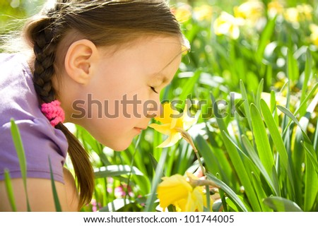 Portrait of a cute little girl smelling flowers outdoors - stock photo