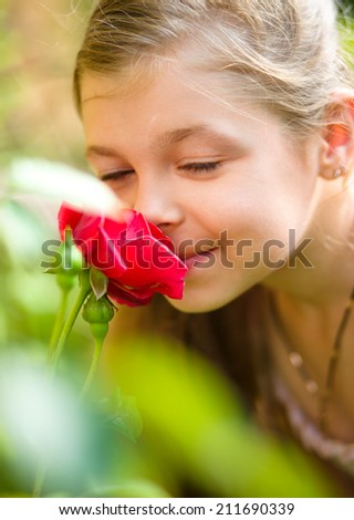 Portrait of a cute little girl smelling rose, outdoor shoot - stock photo