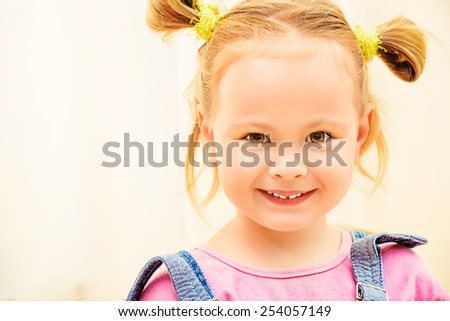 Portrait of a cute little girl smiling at camera. Happy childhood. - stock photo