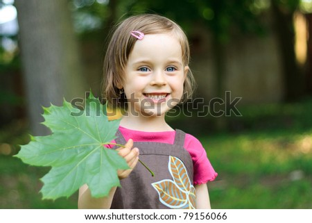 Portrait of a cute little girl with a maple leaf - stock photo