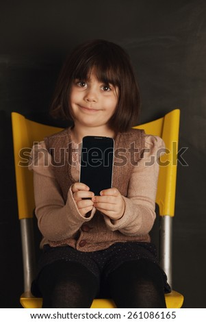 portrait of a cute little girl with a smart phone.focus on the phone - stock photo