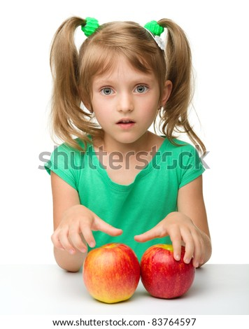 Portrait of a cute little girl with two red apples, isolated over white - stock photo