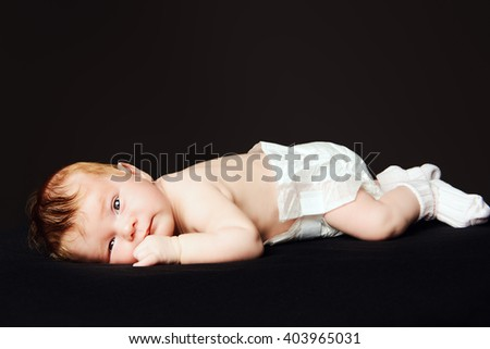 Portrait of a cute little newborn baby. Black background.