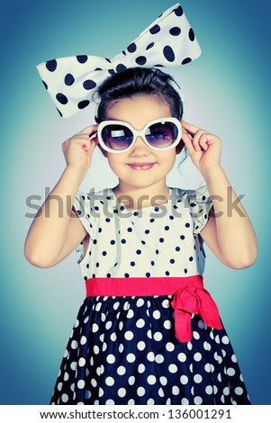 Portrait of a cute little pin-up girl in a beautiful dress and big bow. - stock photo