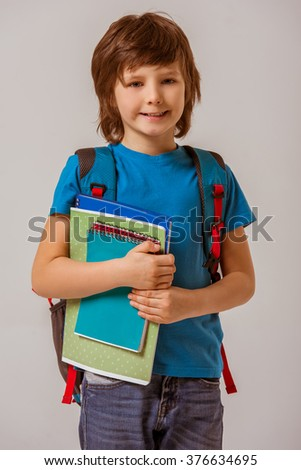 Portrait of a cute little schoolboy in a blue t-shirt with a backpack holding books, looking in camera and smiling while standing on a gray background - stock photo