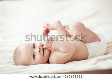 Portrait of a cute 3 months baby lying down on a blanket - stock photo