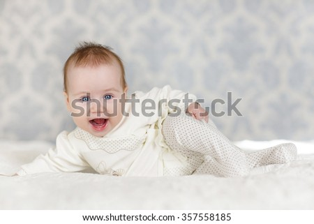 Portrait of a cute 3 months baby lying down on a blanket. happy baby lying on white sheet and holding his legs. baby girl smiling. Portrait of a crawling baby on the bed in her room - stock photo