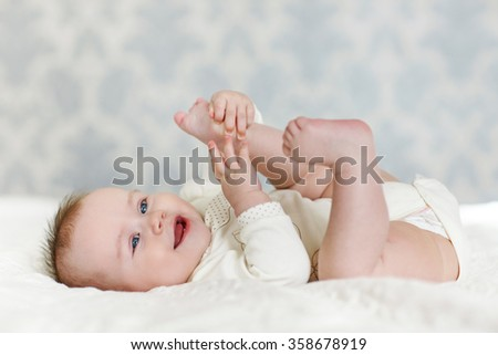 Portrait of a cute 4 months baby lying down on a blanket. happy baby lying on white sheet and holding his legs. baby girl smiling. Portrait of a crawling baby on the bed in her room