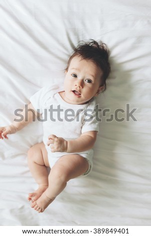 Portrait of a cute 4 months old baby lying down on a bed, top view - stock photo