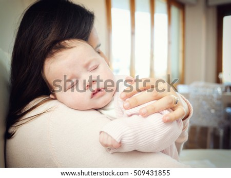 Portrait of a cute newborn baby girl sleeping on her mother's shoulder at home