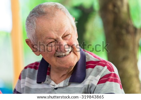 portrait of a cute old man at park - stock photo