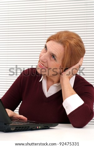 portrait of a cute old woman with computer