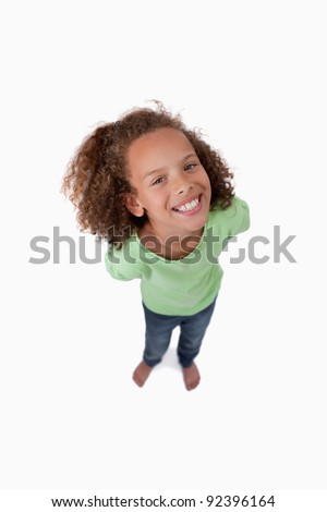 Portrait of a cute playful girl smiling at the camera against a white background