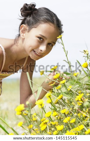 Portrait of a cute preadolescent girl bending down to smell flower in field - stock photo