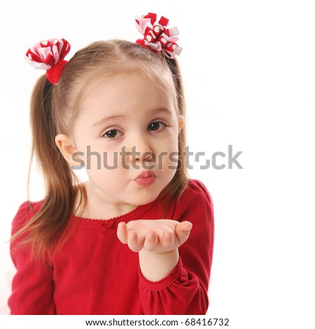Portrait of a cute preschool girl blowing a kiss, wearing red and pigtails dressed for Valentines day - stock photo