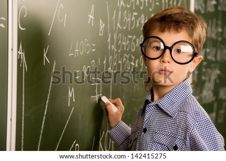 Portrait of a cute schoolboy in round glasses writing on a blackboard in a classroom. - stock photo
