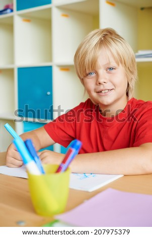 Portrait of a cute schoolboy looking at camera while drawing - stock photo