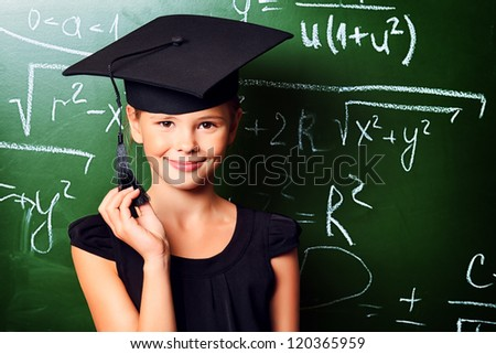 Portrait of a cute schoolgirl in academic hat and big round spectacles at a classroom. - stock photo