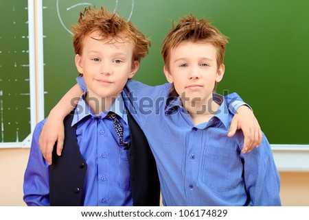 Portrait of a cute shaggy schoolboys in a classroom. - stock photo