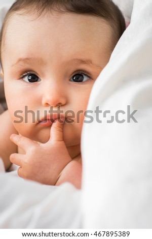Portrait of a cute six-month baby lying in a white bed