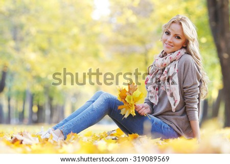 Portrait of a cute smiling woman sitting on autumn leaves in park