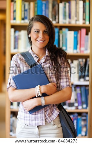 Portrait of a cute student posing with a book in the library - stock photo