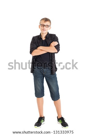 Portrait of a cute teenage boy wearing a black shirt, denim shorts and sneakers. The boy wearing glasses. Folded his arms across his chest. Studio shot, isolated on white background. - stock photo