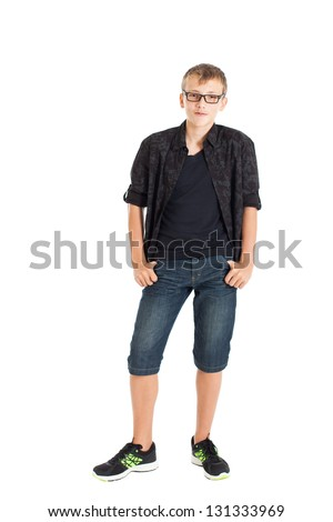 Portrait of a cute teenage boy wearing a black shirt, denim shorts and sneakers with headphones on his shoulders. Studio shot, isolated on white background. - stock photo