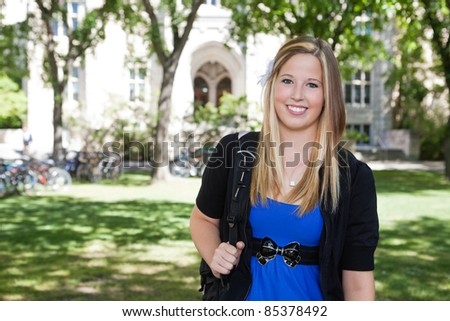 Portrait of a cute teenage girl holding backpack
