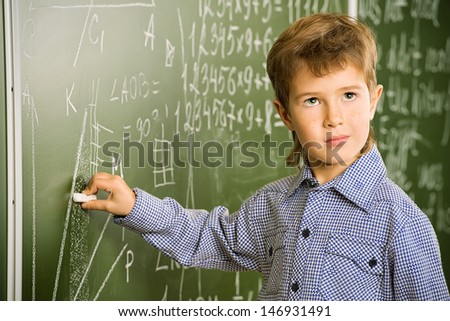 Portrait of a cute thoughtful schoolboy writing on a blackboard in a classroom. - stock photo