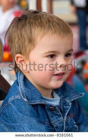 Portrait of a cute toddler boy in a luna park