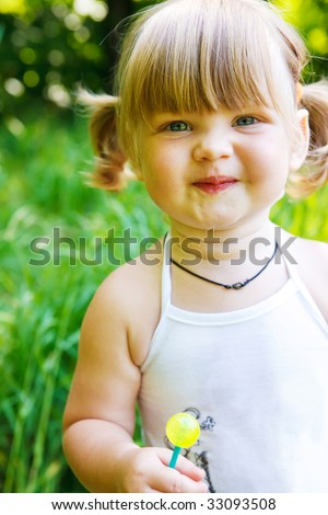 Portrait of a cute toddler holding a lollipop - stock photo