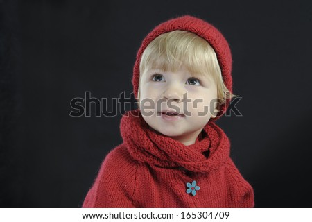 portrait of a cute toddler with knitted hat on black - stock photo