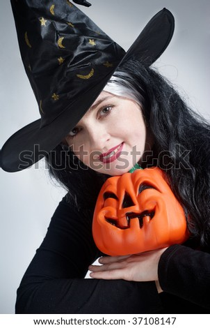 Portrait of a cute witch with hat with a pumpkin
