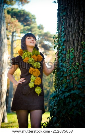 Portrait of a cute woman dressed in handmade knitted dress and scarf. - stock photo