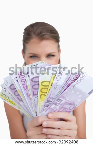 Portrait of a cute woman showing bank notes against a white background - stock photo