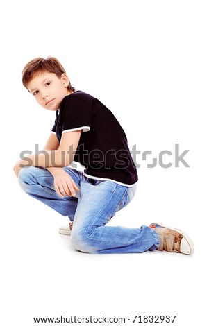Portrait of a cute 9 year boy sitting on a floor. Isolated over white background. - stock photo