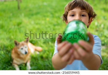 Portrait of a cute 5 year old boy drinking water from a green bottle with a big dog watching in the background - stock photo