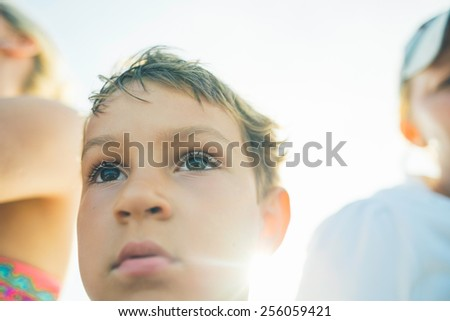 Portrait of a cute 5 year old boy sitting with 2 women in the sun, looking in the distance - stock photo