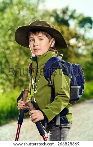 Portrait of a cute 7 years old boy in tourist clothes posing outdoor. Summer day.  - stock photo