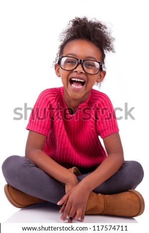 Portrait of a cute young African American girl seated on the floor - stock photo