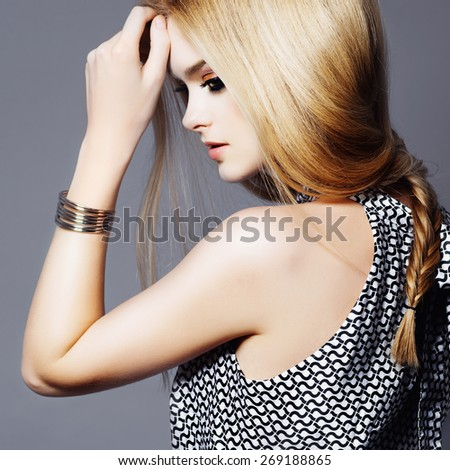 Portrait of a cute young blond woman in a dress with long hair in a studio on a gray background, the concept of health and beauty - stock photo