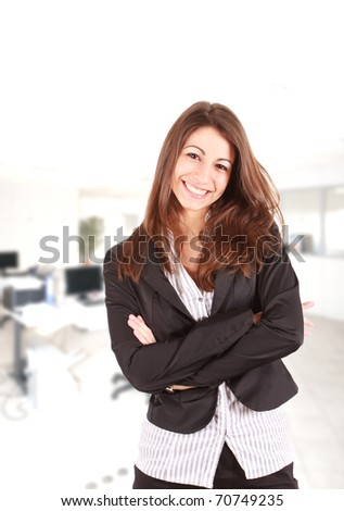 Portrait of a cute young business woman smiling, in an office environment - stock photo