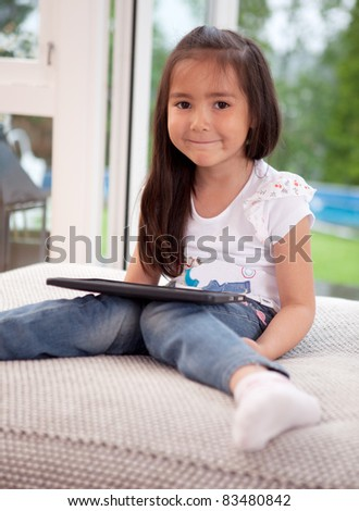 Portrait of a cute young child at home using a digital tablet, looking at the camera - stock photo