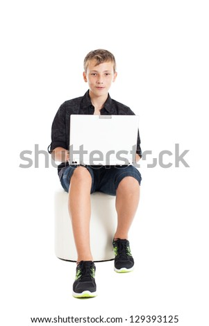 Portrait of a cute young European guy. A guy wearing a black shirt and shorts is sitting with a laptop on your lap. Studio shot, isolated on white background. - stock photo